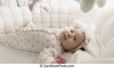 Adorable newborn baby girl in her cot - Newborn baby girl in...