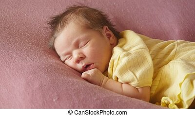Adorable newborn baby in yellow knitted dress sleeping