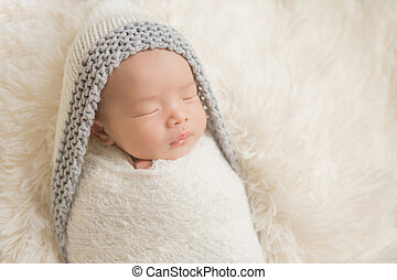 Adorable newborn baby sleeping in cozy room.