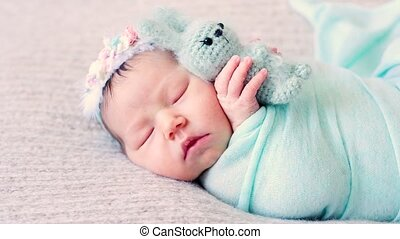 Adorable newborn lies on bed with favorite plush toy -...