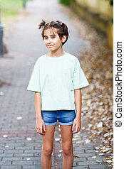 Nine-year-old girl standing in a city park