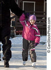 Adorable preschooler (4 years old) iceskating for the first time, holding her father's hand