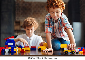 Adorable redhead boy playing with construction set