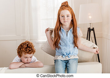 adorable redhead sister and brother sitting together on sofa at home