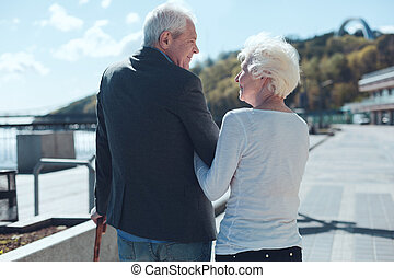 Adorable retired wife and husband smiling to each other