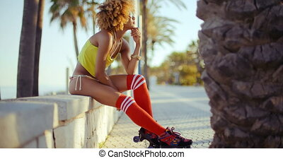 Adorable Roller Skate Girl Sitting at Beach Promenade. She...