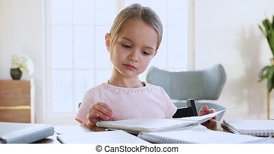 Adorable schoolgirl holding exercise book checking homework sit at desk