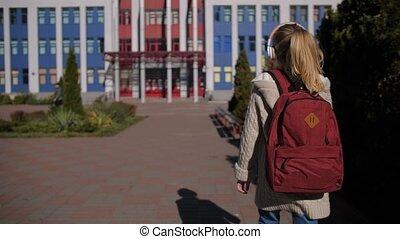 Adorable schoolgirl walking towards school building - Rear ...