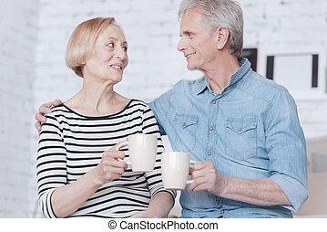Adorable senior couple drinking tea at home