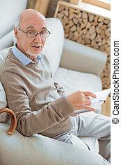 Adorable senior man studying book