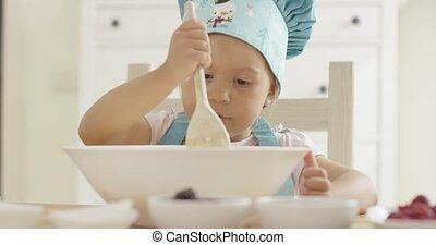 Adorable serious toddler at mixing bowl - Adorable toddler...