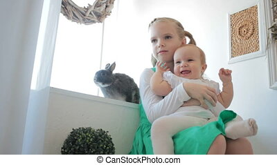 Adorable sister hugging her sister brother at home