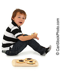 Adorable six year old Caucasian boy sitting on floor eating sugar cookies with chocolate center.