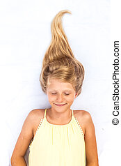 adorable sleeping child with healthy and strong long blond hair in shape of bonfire spike