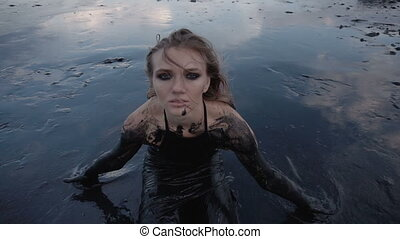 Adorable Slender Blonde Get Smeared with a Black Mud looks...
