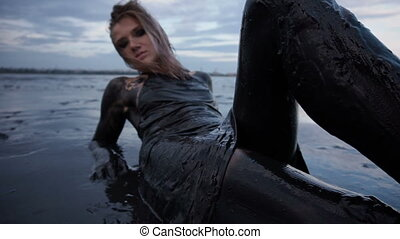 Adorable Slender Blonde Lays Smeared in a Black Mud looks...