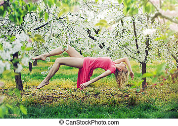 Adorable slim lady levitating in the orchard