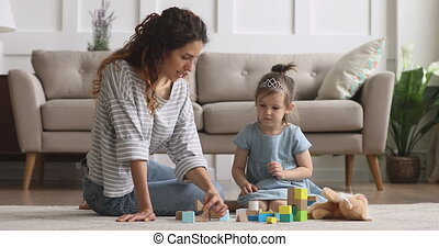 Adorable small kid girl wearing crown playing with nanny.