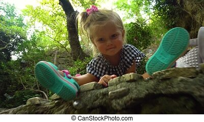 Adorable smiling girl sitting on rock in the forest