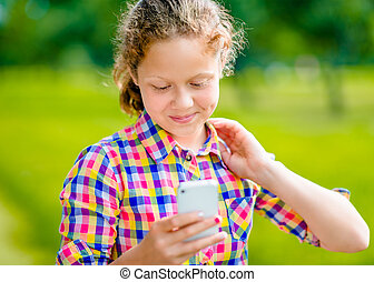 Adorable smiling teenage girl in casual clothes with smartphone in her hand, looking at screen, reading a message, using Facebook in sunny day in summer park