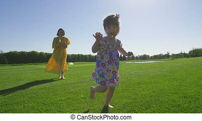 Adorable special needs girl running on green grass -...