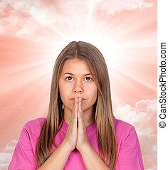 Adorable teen girl praying
