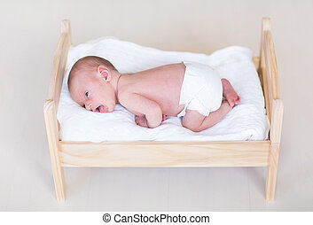 Adorable tiny newborn baby in a wooden toy bed