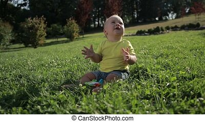 Adorable toddler baby boy clapping hands outdoors