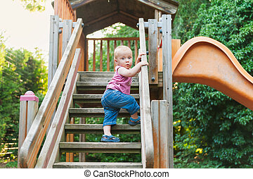 Adorable toddler boy having fun on playground, climbing on a slide
