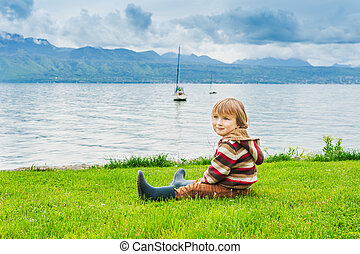 Adorable toddler boy resting by the lake on a cloudy day