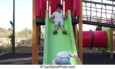 Adorable toddler climbing on the slide while his brother is trying to slide down. Slow motion