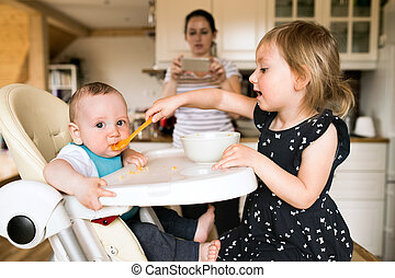 Adorable toddler girl at home feeding her baby brother.