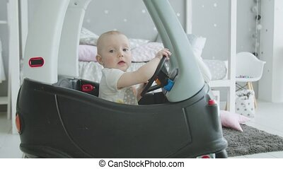 Adorable toddler girl driving toy baby car at home