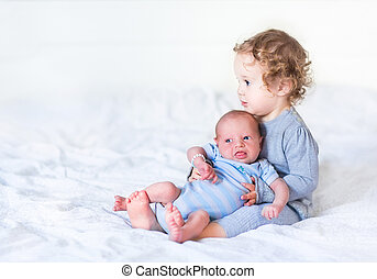 Adorable toddler girl holding her newborn baby brother