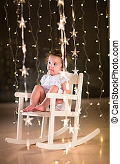 Adorable toddler girl in a white dress sitting in a white rockin