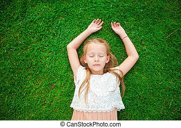 Adorable toddler girl on green grass