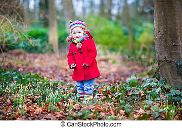 Adorable toddler girl playing with first snowdrop flowers in a b