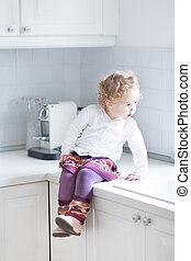Adorable toddler girl sitting in a white kitchen on the countert