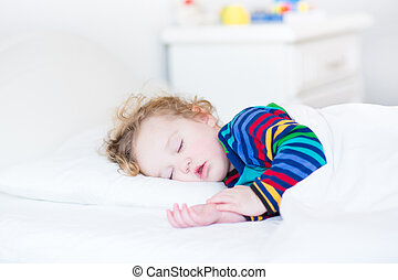 Adorable toddler girl taing a nap in a white sunny bedroom