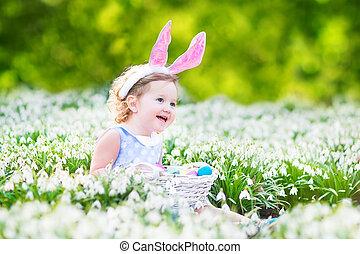 Adorable toddler girl wearing bunny ears playing with Easter...