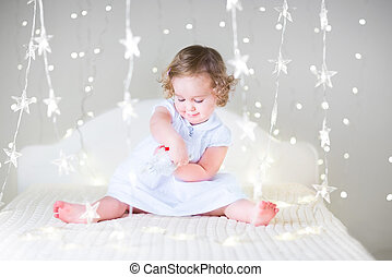 Adorable toddler girl with curly hair wearing a white dress is p