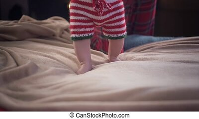 Adorable toddler in striped Christmas pants and cap is making his first steps on beige bed and smiling