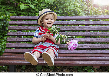 Adorable toddler playing with a flower