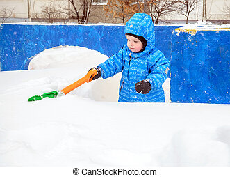 Adorable tree year old boy shoveling snow