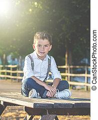 Adorable trendy kid posing in park