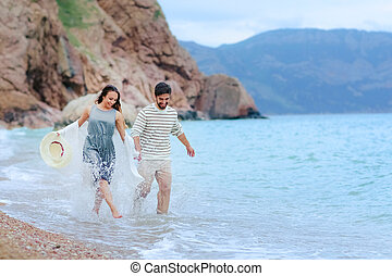 Adorable wedding couple holds each other hands walking along the beach against the rocks and ocean