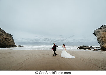 Adorable wedding couple walking along the beach, reflecting in the water. Panoramic view.