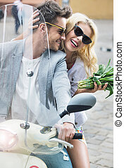 Adorable woman sitting on the scooter with her boyfriend