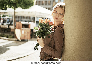 Adorable woman with a bouquet of roses