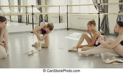 Adorable young ballet dancers are putting on ballet slippers...